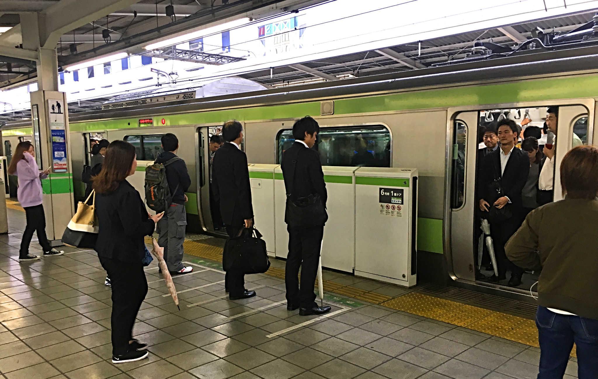 Sur le quai du métro, tout le monde se met en file indienne pour attendre la rame