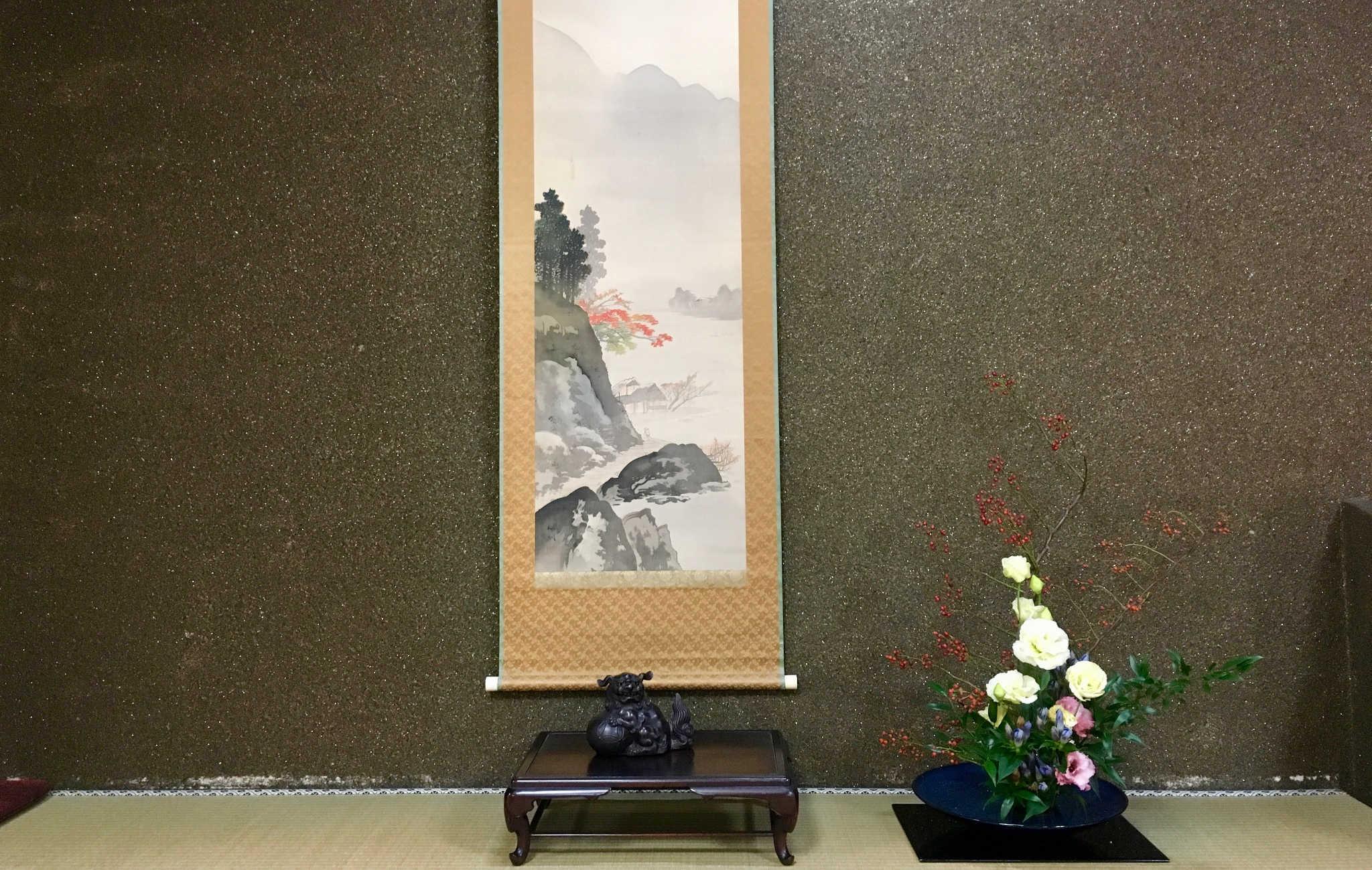 Dans un tokonoma, un kakemono avec un paysage d'automne et une composition florale