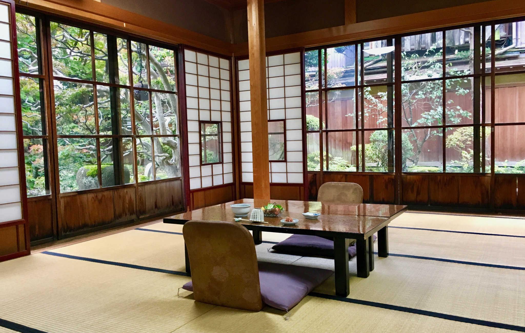 Magnifique salle avec tatamis au sol et vue sur un petit jardin