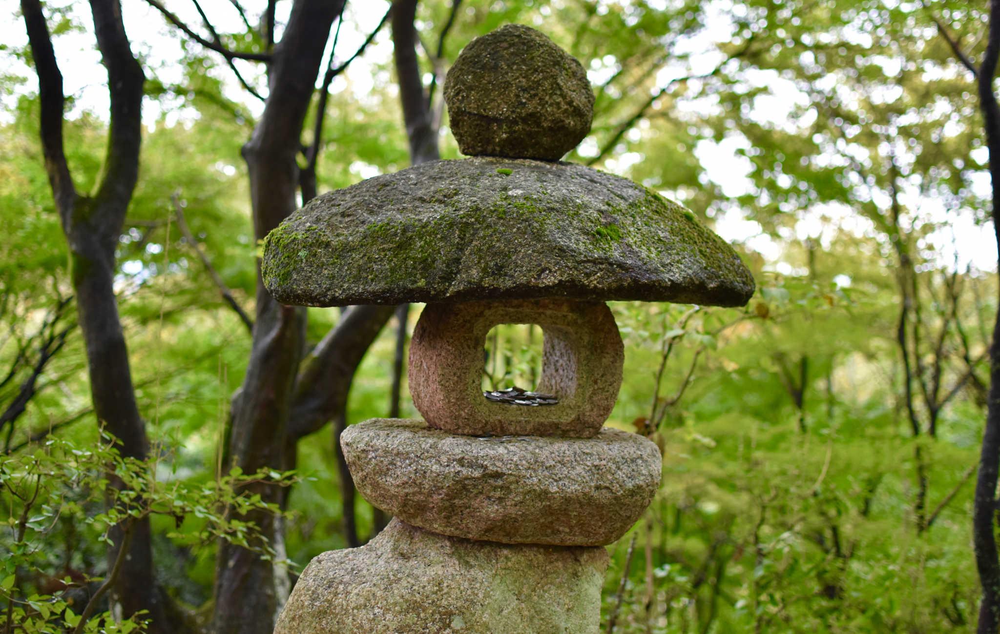 Lanterne en pierre brute, des pièces de monnaie y sont disposées en offrande