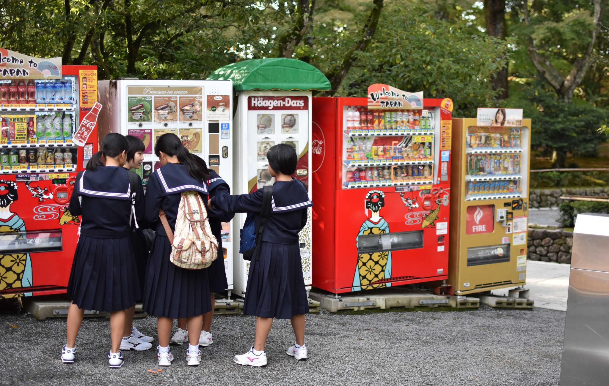 Des écolières devant des distributeurs de boisson, situés juste à à l'entrée du temple