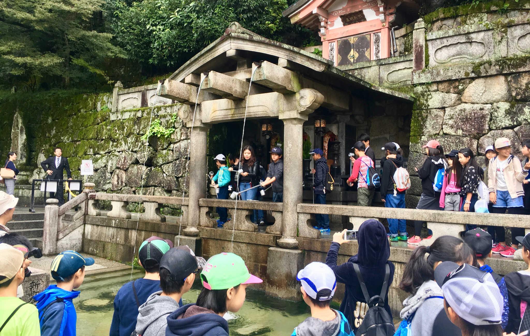 Des écoliers font la queue pour prendre de l'eau, symbole du temple
