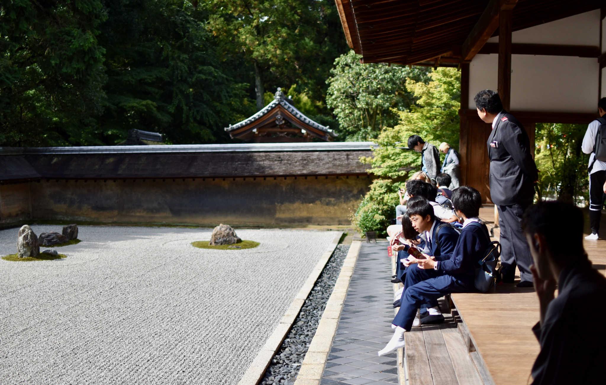 Des écoliers contemplent le jardin de pierres