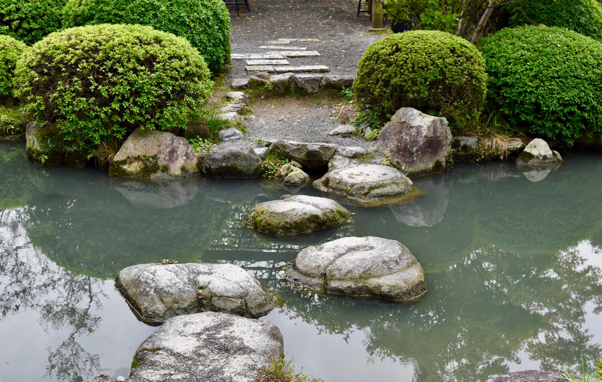 De grosses pierres servent de pas japonais pour franchir l'eau