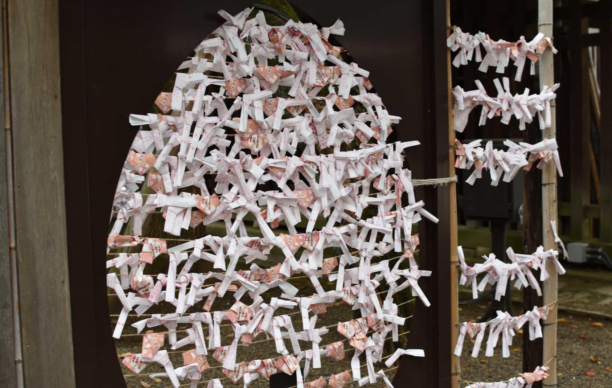 Les petits morceaux de papier sont pliés et noués sur des fils pour conjurer le mauvais présage