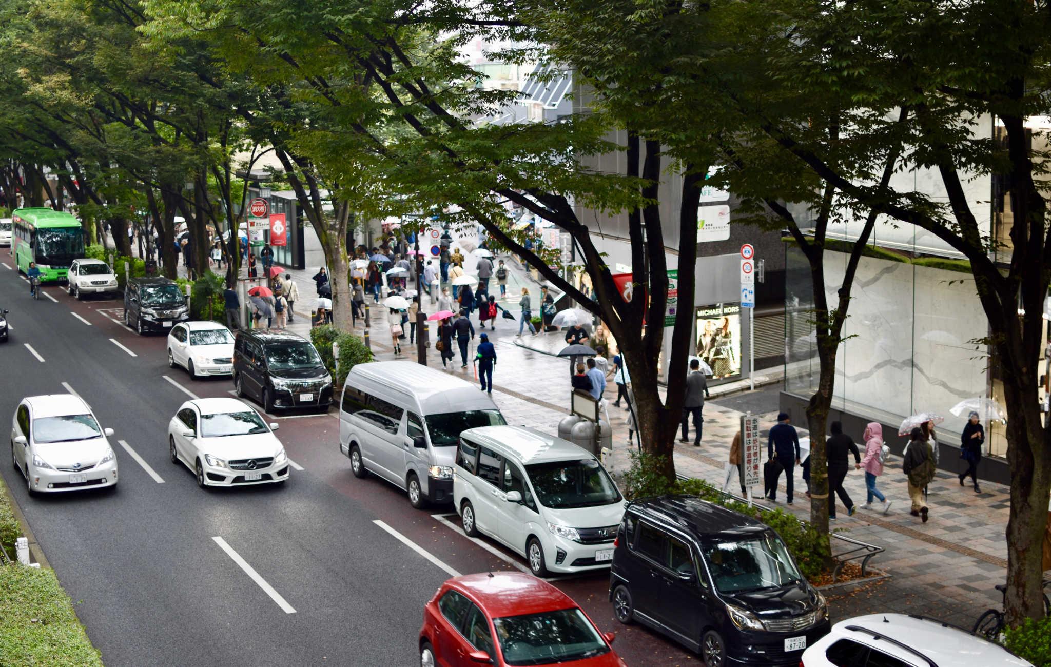 Beaucoup de monde et de voitures dans la rue principale